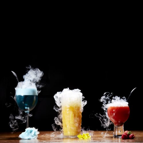 square-crop-dry-ice-cocktails-three-drinks-blue-yellow-red-wooden-table-black-background